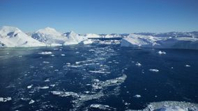 Filmando com um zangão em Gronelândia, vista para o mar com iceberg enormes filme