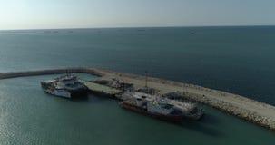 filmar aéreo do vídeo 4K de navios de recipiente fixos no porto de Bautino nas costas do mar Cáspio, Cazaquistão vídeos de arquivo