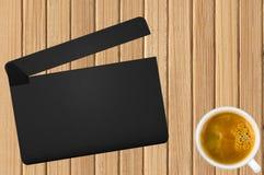 Filmclapper och kaffekopp på träbakgrund Arkivfoto