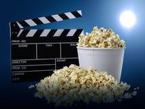 Filmclapperboard och popcorn på på blå bakgrund arkivfoton