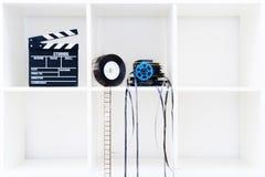 Filmclapperbräde och filmrullar på den vita bokhyllan Arkivbilder
