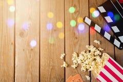 Filmclapperbräde och popcorn på träbakgrund Den moderna yrkesmässiga filmkameran med Mattebox och följer fokusen på abstrakt utry Arkivbilder