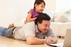 Filme de And Daughter Watching do pai no portátil em casa Fotos de Stock