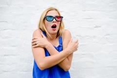 Filme de observação da jovem mulher bonita com os vidros 3D, excitando guardando as mãos Fotografia de Stock