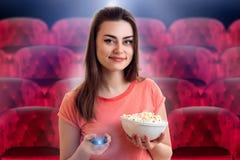 Filme de observação da menina com pipoca no cinema fotografia de stock
