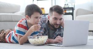 Filme de observação do pai e do filho no portátil
