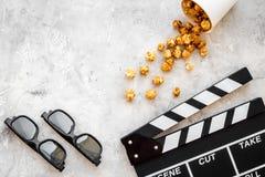 Filme de observação no cinema Clapperboard, vidros e pipoca no copyspace cinzento da opinião superior do fundo Fotografia de Stock Royalty Free