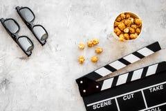 Filme de observação no cinema Clapperboard, vidros e pipoca no copyspace cinzento da opinião superior do fundo Fotos de Stock