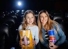 Filme de observação surpreendido da mãe e da filha Foto de Stock Royalty Free