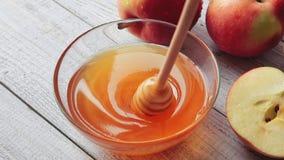 Filme do gotejamento do mel Maçãs na tabela de madeira Alimento tradicional da celebração pelo ano novo judaico Conceito Rosh Has video estoque