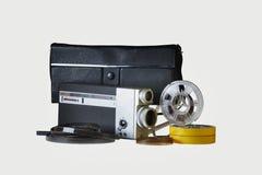 Filme la cámara 8m m con su bolso, carretes y tiras de la película imágenes de archivo libres de regalías