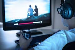 Filme ou série de observação do indivíduo em linha de fluir o serviço e de beber a lata da soda Vídeo por encomenda do Internet n foto de stock