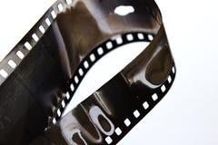 Filme preto e branco velho em uma espiral sobre o fundo branco Filme retro velho Filme preto e branco muito velho Imagem de Stock