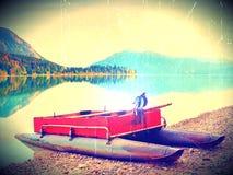 Filmeffekt Övergiven röd grå fiskebåt på banken av den alpina sjön Höstlig morgon på sjön i försiktigt solljus Royaltyfria Bilder