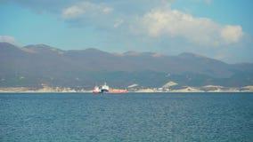 Filmen der Bewegung eines Frachtschiffs in der hohen See vor dem hintergrund eines anderen Schiffs, Berge, Meeres und Himmels stock video footage
