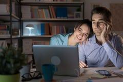 Filmes de observação dos pares felizes em linha Fotografia de Stock Royalty Free