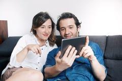 Filmes de observação dos pares felizes na tabuleta digital foto de stock royalty free