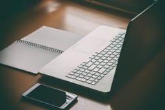 Filmez le carnet d'ordinateur de ton avec le smartphone et le carnet sur le bois Images libres de droits
