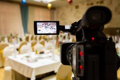 Filming of the event. Videography. Served tables in the Banquet hall.  Royalty Free Stock Photography