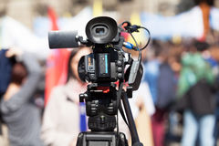 Filming female reporter with a video camera, blurred crowd in the background. Filming female journalist with a television camera, blurred people in the Royalty Free Stock Photos