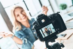Filming. Beautiful young woman in casual wear smiling while recording video stock photos
