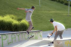 Filming the jump of a skater. A guy is filming his buddy jumping with a sketeboard stock photos