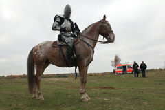 Filming of the new movie The Knights. MILOVICE, CZECH REPUBLIC - OCTOBER 23, 2013: Actor dressed as a medieval knight rides a horse during the filming of the new stock images