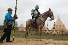 Filming of the new movie The Knights. MILOVICE, CZECH REPUBLIC - OCTOBER 23, 2013: Actor dressed as a medieval knight rides a horse during the filming of the new stock photography
