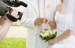 Filming a newly-married couple. Operator films a happy newly-married couple Royalty Free Stock Images