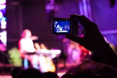 Filming Rock show. Fan filming a rock show Stock Image
