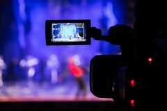 Filming the show from the auditorium. LCD viewfinder on the camcorder. Theatrical performance. The actors on stage Stock Image