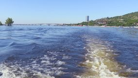 Filming from the stern of the ship. Summer river landscape. The Volga river in Saratov, Russia. Road bridge between the cities of Saratov and Engels. The sound stock video footage