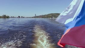 Filming from the stern of the ship. Summer river landscape. The Volga river in Saratov, Russia. Russian flag, the tricolor. Road bridge between the cities of stock video