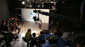 Filming in TV studio. Filming in a television studio, cameramen, directors and actor working stock video footage