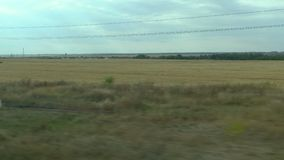 Filming from the window of a moving train. Russian autumn landscape: fields, forests, planting, sky.  stock footage