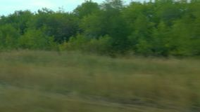 Filming from the window of a moving train. Russian autumn landscape: fields, forests, planting, sky.  stock video footage