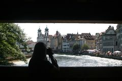 Filming woman upon a bridge over the river Reuss in Luzern. View from the Spreuerbrücke on the bank of the Reuss with the market and the Jesuitenkirche in Royalty Free Stock Photos