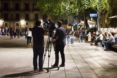 Filming Work of operator on street at night. Spain, Barcelona - October 8, 2017: Filming Work of operator on street with artificial light at night, night royalty free stock image