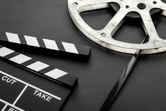 Filmings concept. Clapperboard and film stock on black background copy space stock photo