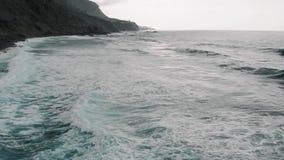 Filmisk flyg- sikt Norrkusten av Tenerife, stranden och många havvågor som bildar skum kanarief?gel?ar spain arkivfilmer