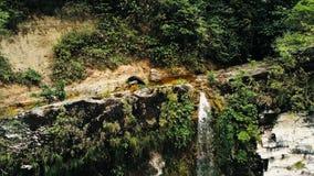 Filmiskt flyg- surrfoto av vattenfallet och en liten pöl djupt i rainforestdjungeln på den Amboro nationalparken, Bolivia royaltyfria foton