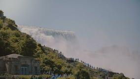 Filmiskt POV-skott av turister i regnrockar som går upp stegen på den episka härliga Niagara Falls vattenfallet på solig dag lager videofilmer