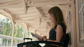 Filmiskt skott av den unga kvinnan som läser en bok på järnvägstationen med resväskan lager videofilmer