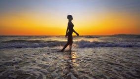 Filmiskt skott av kvinnan som går på vatten arkivfoto