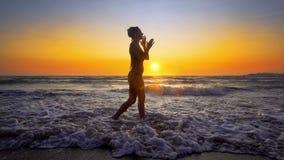 Filmiskt skott av kvinnan som går på vatten på solnedgången royaltyfria foton