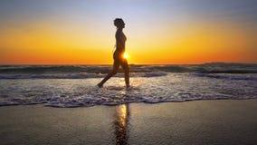 Filmiskt skott av kvinnan som går på vatten på solnedgången fotografering för bildbyråer