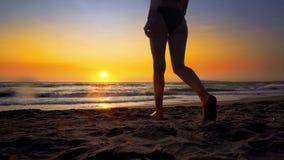 Filmiskt skott av kvinnan som går på vatten på solnedgången arkivbild