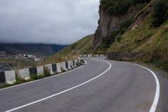 Filmiskt väglandskap Asphalt Road throuth bergen Med den molniga skyen arkivfoto
