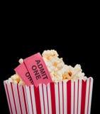 Filmkarte und -popcorn auf einem schwarzen Hintergrund Lizenzfreies Stockbild