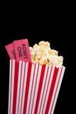 Filmkarte und -popcorn auf einem schwarzen Hintergrund Lizenzfreies Stockfoto